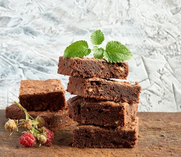 Pila di pezzi quadrati al forno di torta brownie al cioccolato