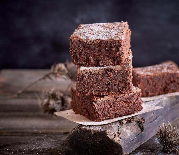 Pila di pezzi quadrati di torta brownie marrone al forno