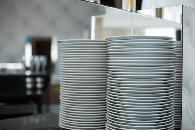 Pila di piatti bianchi puliti in un ristorante. l'evento prepara i dettagli