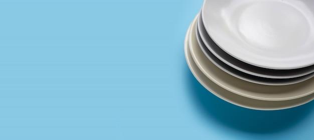 Pila di piatti su fondo blu.