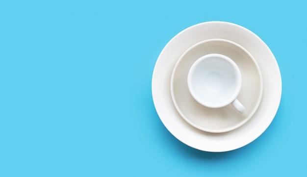Pila di piatto, ciotola e tazza su fondo blu.