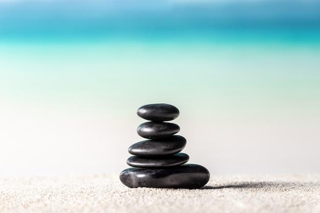 Pila di pietre di zen sulla spiaggia di sabbia