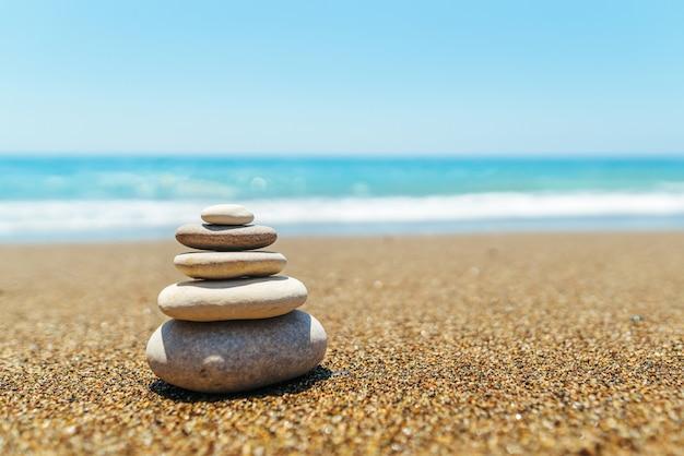 Pila di pietre sulla spiaggia vicino al mare