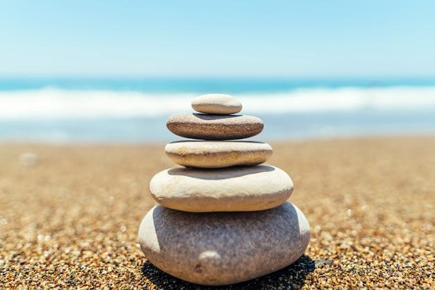Pila di pietre zen sulla spiaggia vicino al mare