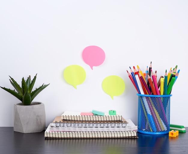 Pila di quaderni a spirale e adesivi colorati, accanto a un vaso di ceramica con un fiore
