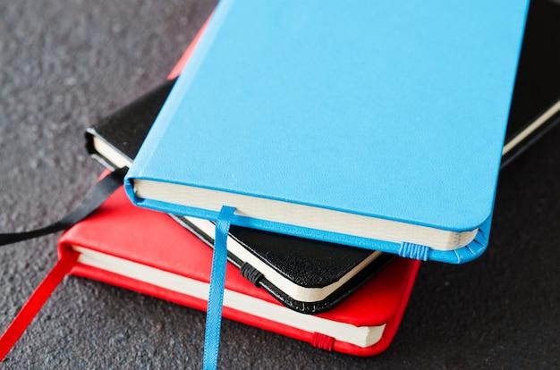 Pila di quaderni colorati per la scrittura o libri su sfondo scuro
