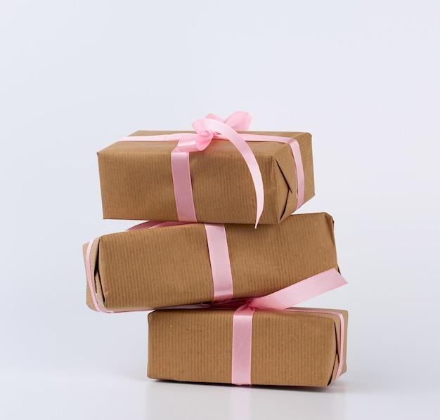 Pila di regali in scatole avvolte in carta kraft marrone e legate con nastro di seta rosa
