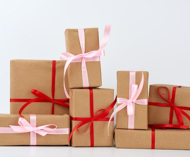 Pila di regali in scatole avvolte in carta kraft marrone e legate con nastro di seta su un bianco