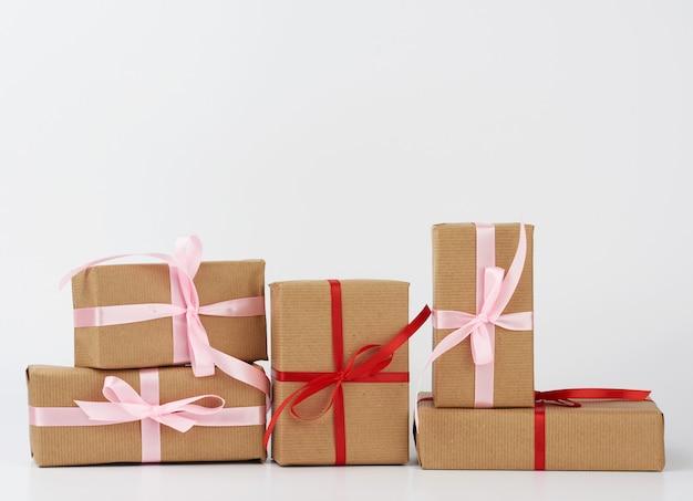 Pila di regali in scatole avvolte in carta kraft marrone e legate con nastro di seta