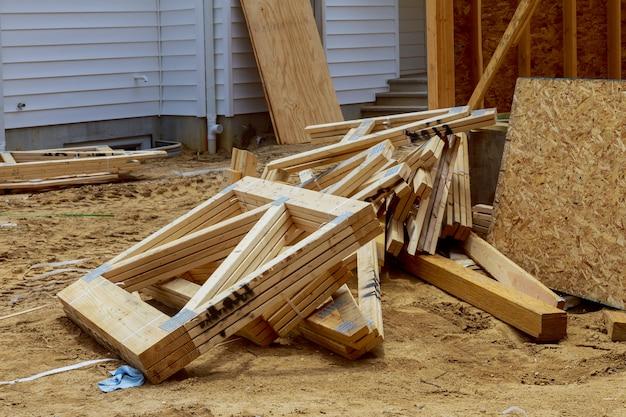Pila di scarico delle travi di legno sulla costruzione della costruzione dai materiali da costruzione della trave