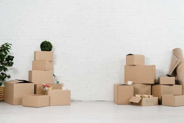 Pila di scatola commovente in nuova casa contro il muro di mattoni bianco