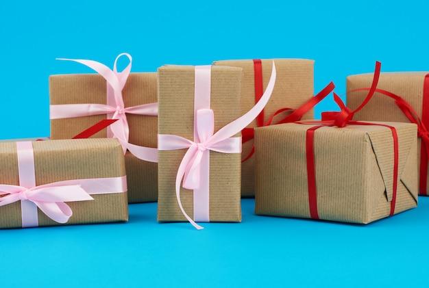 Pila di scatole avvolte in carta marrone e legate con un fiocco rosso, regali su un blu. ottimo design per qualsiasi scopo