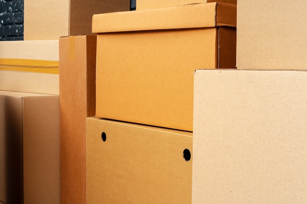 Pila di scatole di cartone nella stanza vuota contro il muro di mattoni nero