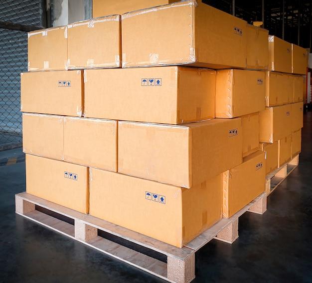 Pila di scatole di cartone su pallet di legno. esportazione merci, spedizione, magazzino spedizioni.