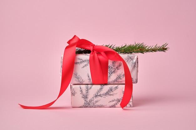 Pila di scatole regalo rosa avvolto e legato con un fiocco rosso