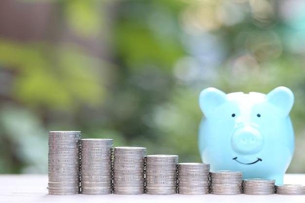 Pila di soldi delle monete su verde naturale