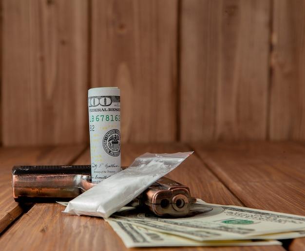 Pila di soldi, droghe e una pistola su un tavolo di legno, concetto di pericolo e minaccia del farmaco