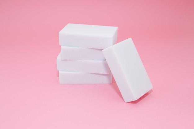 Pila di spugne per famiglie con quattro spugne per la pulizia su sfondo rosa.