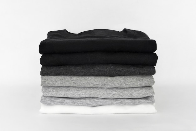 Pila di t-shirt nera, grigia e bianca piegata