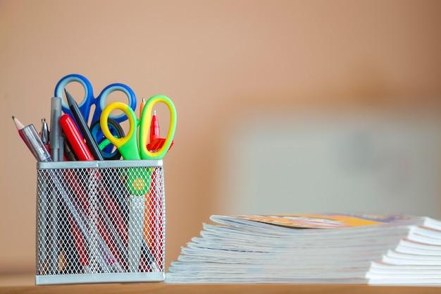 Pila di taccuini e disposizione della cancelleria in aula o in ufficio sul fondo dello spazio della copia