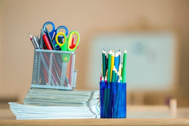 Pila di taccuini, matite colorate di disegno e disposizione della cancelleria su copyspace.