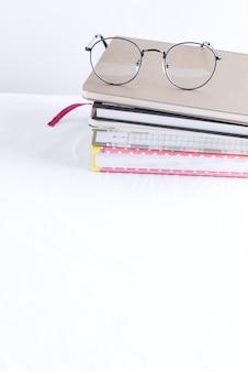Pila di taccuini per note e annotazioni con gli occhiali in alto su un tavolo bianco.