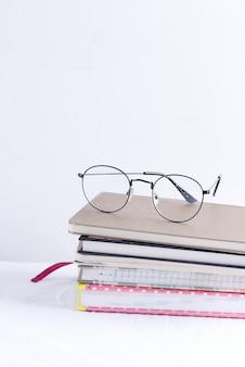 Pila di taccuini per note e annotazioni con gli occhiali in alto su un tavolo bianco