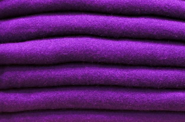 Pila di tendenza maglioni di lana ultravioletti primo piano, trama, sfondo