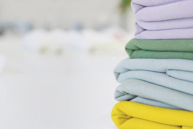 Pila di tessuti per cucire sul tavolo. tessuti multicolor per la sartoria. un mucchio di tessuti per cucire