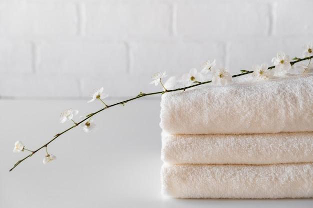 Pila di tre asciugamani da bagno bianchi soffici con ramo. composizione spa copia spazio