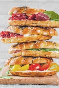 Pila di vari panini bagel fatti in casa con semi di sesamo e papavero, crema di formaggio, prosciutto, ravanello, rucola, pomodorini, cetrioli, superficie strutturata bianca grigia