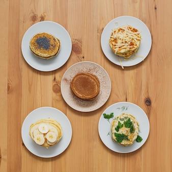 Pila di varie frittelle sul tavolo di legno, piatto laici