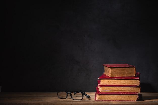 Pila di vecchi libri e vetri sulla tavola di legno sulla parete nera del cemento