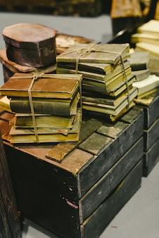 Pila di vecchi libri immagazzinati in rovina su un vecchio tronco d'annata.
