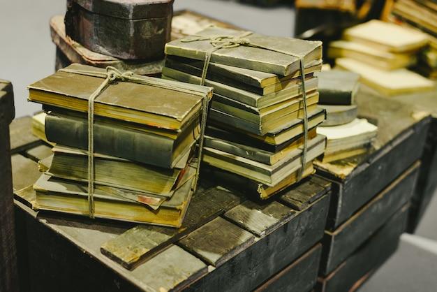 Pila di vecchi libri memorizzati in rovina su un vecchio tronco d'epoca.