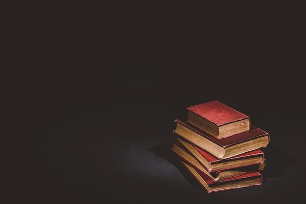 Pila di vecchi libri su sfondo nero, tono vintage