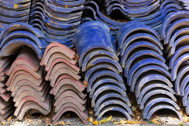 Pila di vecchie mattonelle di tetto blu per costruzione