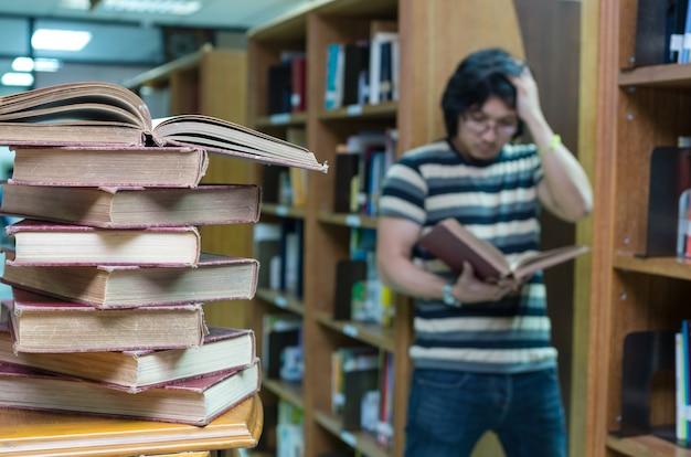 Pila di vecchio libro sullo scrittorio in biblioteca con l'uomo che legge sopra il fondo della sfuocatura del libro