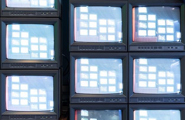 Pila di vecchio monitor analogico della televisione con il programma in diretta del segnale nello studio di radiodiffusione, retro schermo televisivo del tubo della tv