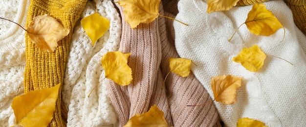 Pila di vestiti a maglia con foglie di autunno, concetto di autunno inverno.