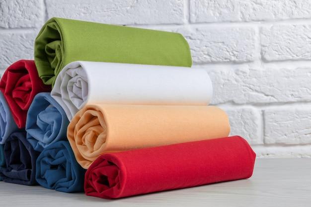 Pila di vestiti rotolati colorati su una tavola di legno leggera. avvicinamento