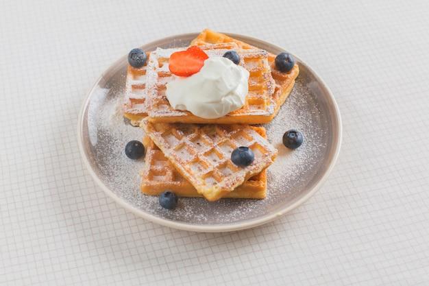Pila di waffle guarniti con fragole; mirtillo e panna montata sul piatto sopra la tovaglia