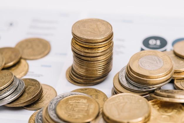 Pila dorata di monete sopra il modello di infografica