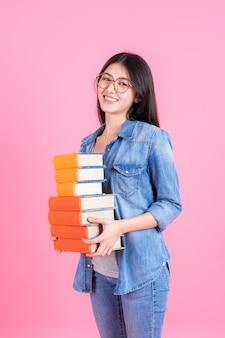 Pila graziosa adolescente della tenuta della ragazza del ritratto di libri e di smiley sul rosa, concetto del teenge di istruzione