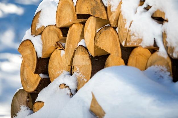 Pila ordinatamente accatastata di legno secco tagliato dei tronchi coperto di neve all'aperto il giorno soleggiato di inverno freddo luminoso, estratto, ceppi di legno del fuoco preparati per l'inverno, pronti per bruciare.