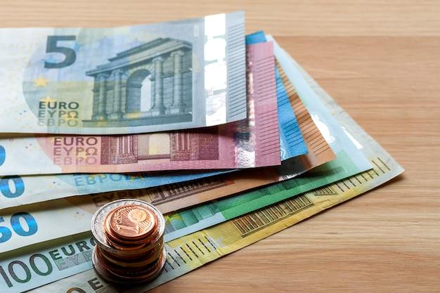 Pila ordinatamente ordinata di banconote in euro, banconote da dieci, venti, uno e duecento euro e monete metalliche diverse. denaro, disponibilità e finanze, concetto di investimento di successo.