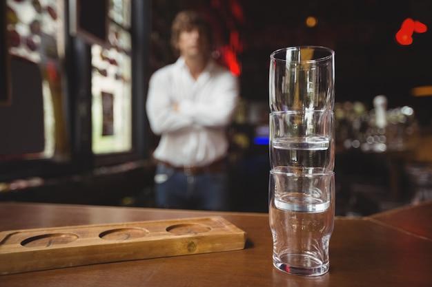 Pila vuota di vetro di birra e vassoio al contatore della barra
