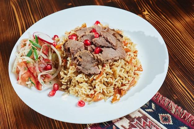 Pilaf asiatico delizioso su un piatto marrone. vista orizzontale dall'alto, stile rustico.