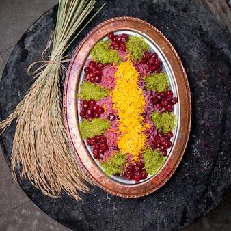 Pilaf colorato vista dall'alto con baccelli di ciliegia e grano in vassoio di rame