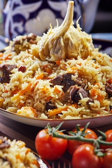 Pilaf uzbeko in un autentico piatto blu e oro, girato su uno sfondo blu con pomodori, aglio e tè